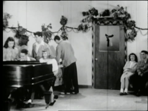 B/W 1950's teenagers playing piano and drinking at party