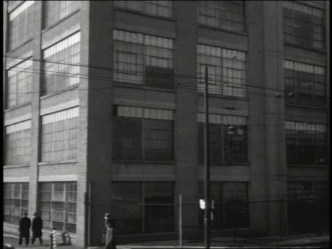 vidéos et rushes de b/w 1940's tilt down + pan from general motors (frigidaire) factory to people + train passing / winter - general motors