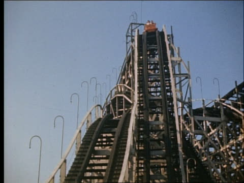 1940's tilt down of crowded roller coaster going downhill / cyclone / coney island - coney island stock-videos und b-roll-filmmaterial