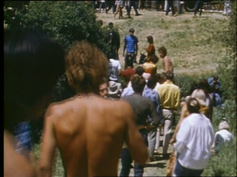 vídeos de stock e filmes b-roll de 1960's tilt up of crowd of hippies at outdoor concert - love in