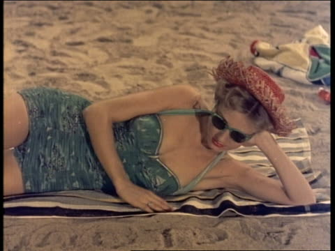 1950's PAN to woman in swimsuit on beach / removes sunglasses + lies down