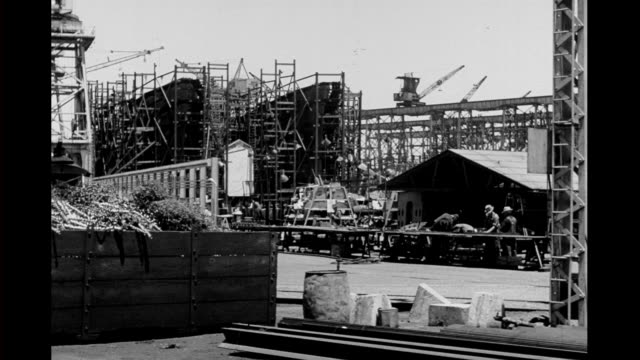 vidéos et rushes de 1940's - tracking shot of shipyard, workers building naval ships - 1942