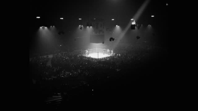 1950's tracking shot of spotlight following boxer walking towards boxing ring - boxing stock videos & royalty-free footage