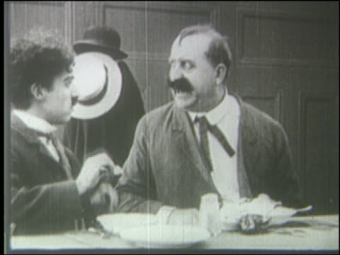 B/W 1910's two men slap each other in faces, throw food in faces + start fighting in diner