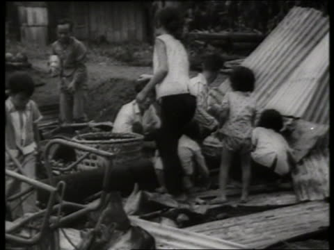 B/W 1960's Vietnamese family cleans up destroyed village / Vietnam / SOUND