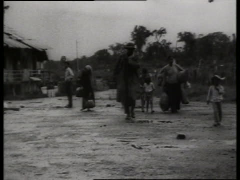 B/W 1960's Vietnamese people leaving destroyed village / Vietnam / SOUND