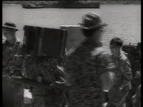 b/w 1960's vietnamese soldiers putting supplies on beach / sound - crate stock videos & royalty-free footage