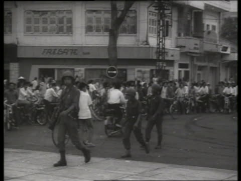 B/W 1960's Vietnamese soldiers walk by people with bicycles / SOUND