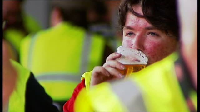 MP's want to see warning labels on alcohol labels ENGLAND London INT 'Campaign for Real Ale' PAN man cutting cable tie Men along past 'Glass Returns'...