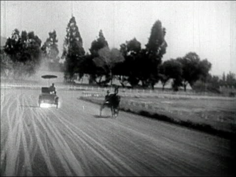 stockvideo's en b-roll-footage met 1910's wide shot car racing horse and carriage on racetrack catching on fire/ audio - paard en wagen