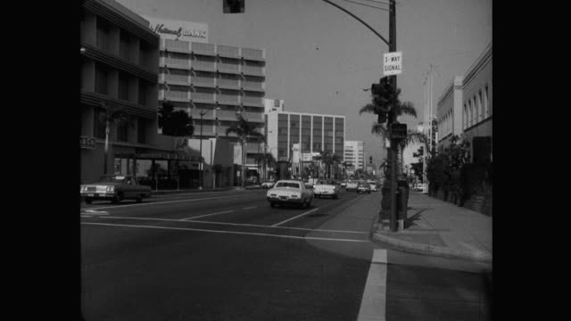 vídeos de stock e filmes b-roll de 1960's - wide shot cars driving on street in downtown, wilshire boulevard, los angeles, california, usa - wilshire boulevard