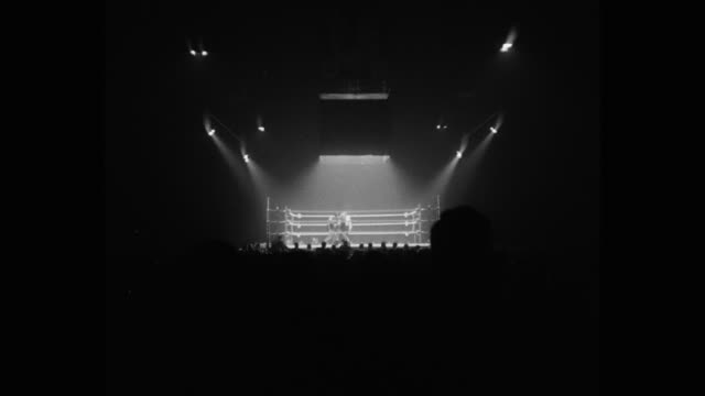 1950's wide shot of boxers competing in boxing ring - 前ボケ点の映像素材/bロール