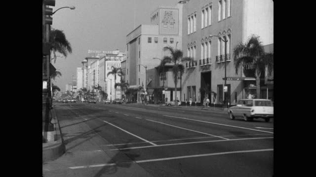 1960's - wide shot of cars driving on wilshire boulevard, beverly hills, los angeles county, california, usa - wilshire boulevard stock videos & royalty-free footage