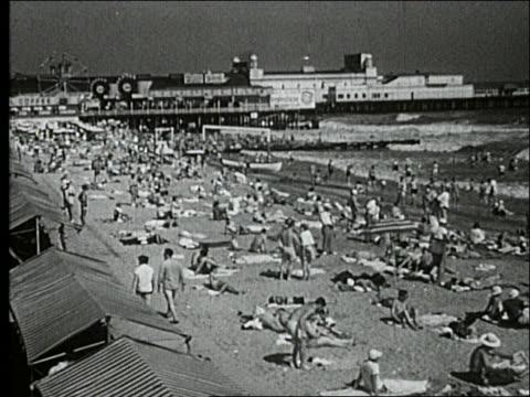 vídeos de stock, filmes e b-roll de b/w 1940's wide shot of crowded beach / pier with amusement park in background / atlantic city - atlantic city