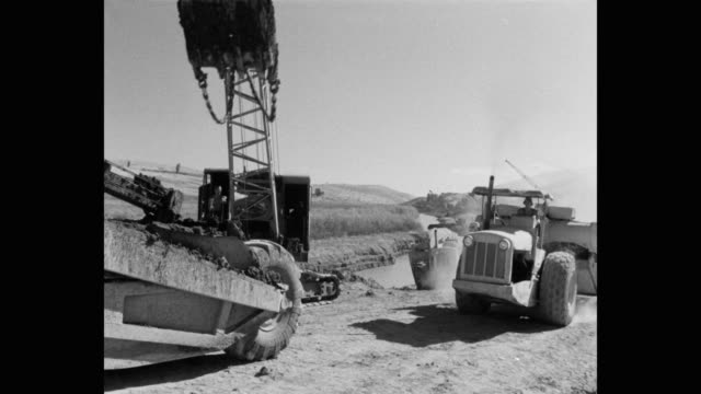 1950's - wide shot of man driving construction vehicle by river - construction vehicle stock videos & royalty-free footage