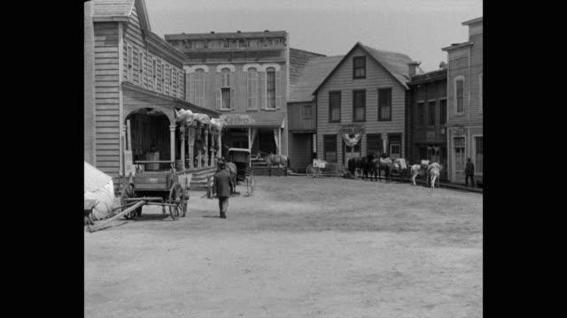 vídeos de stock e filmes b-roll de 1950's - wide shot of men riding horses in west town - animal de trabalho