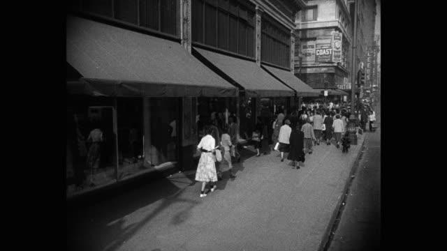 1950's - wide shot of people walking on sidewalk in city, los angeles, california, usa - full suit stock videos & royalty-free footage