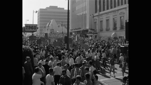 1960's wide shot of protestors protesting on street, los angeles, ca, usa - friedensdemonstration stock-videos und b-roll-filmmaterial
