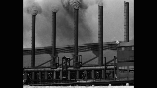 vidéos et rushes de 1930's wide shot of smoke emitting from smoke stacks of steel foundry - aciérie