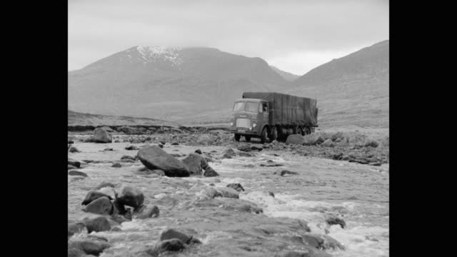 1960's - wide shot of truck driving through river in rural scotland - heavy goods vehicle stock videos & royalty-free footage