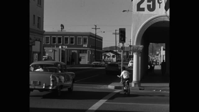 1960's - wide shot of vehicles driving on street in city, venice, ca, usa - santa monica sign stock videos & royalty-free footage
