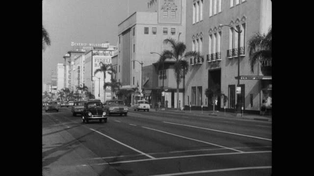 1960's - wide shot of vehicles driving on wilshire boulevard, beverly hills, los angeles county, california, usa - wilshire boulevard stock videos & royalty-free footage