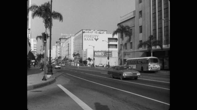 vídeos de stock e filmes b-roll de 1960's - wide shot of vehicles driving on wilshire boulevard, beverly hills, los angeles county, california, usa - wilshire boulevard
