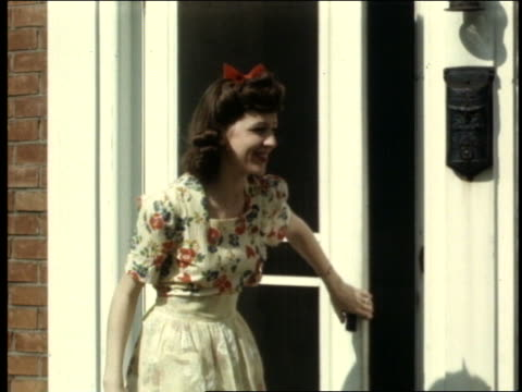 1940's woman coming out of front door + kissing man
