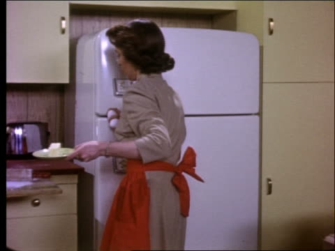 1950's woman takes food from refrigerator, cooks on stove