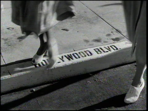 1940's woman walks over 'hollywood blvd' painted on curb - hollywood california stock videos & royalty-free footage
