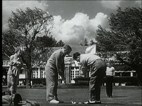 vídeos y material grabado en eventos de stock de b/w 1940's woman watches men putting on green / country clubhouse in background / atlantic city - bandera de golf
