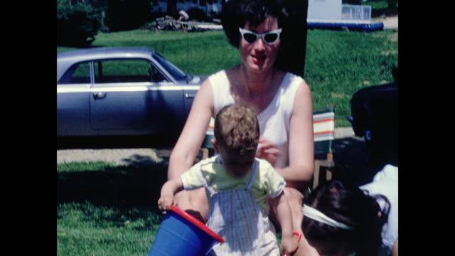 1960's woman with sunglasses, children playing in front lawn - leksak bildbanksvideor och videomaterial från bakom kulisserna