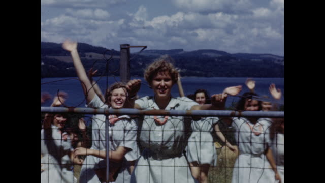 1950's young women in girl scout uniforms open gate and wave - winken stock-videos und b-roll-filmmaterial