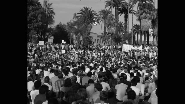 1960's zoom in shot of protestors listening to man giving speech on microphone at public park, los angeles, ca, usa - talking politics stock videos & royalty-free footage