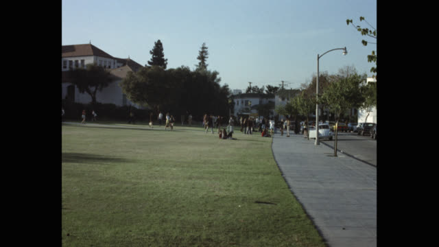 1970's zoom in shot of students walking in beverly hills high school campus, beverly hills, california, usa - beverly hills california点の映像素材/bロール