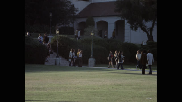 1970's zoom out shot of students walking outside beverly hills high school, beverly hills, california, usa - beverly hills california点の映像素材/bロール