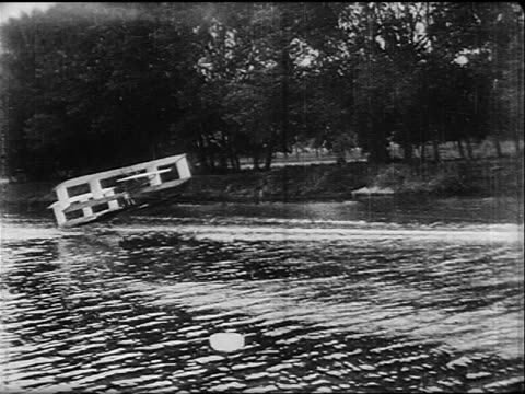 b/w 1900's/10s pan boat pulling early glider attempting to take off on river - motorboat stock videos & royalty-free footage