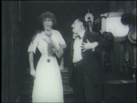 B/W 1910's/20's woman slaps man in face + knocks him on floor by stairs