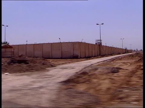 sabotage threatens infrastructure/bomb attack/danish soldier killed; lib iraq: baghdad: ext gv abu ghraib prison track int prison door to corridor... - sabotage stock videos & royalty-free footage