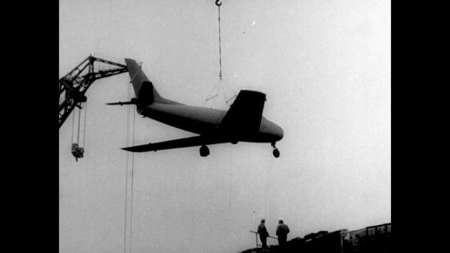 sabre planes with japanese insignia fly in formation / crane lifting airplane / cu underbelly of plane / plane is lowered onto dock as technicians... - us air force stock videos & royalty-free footage