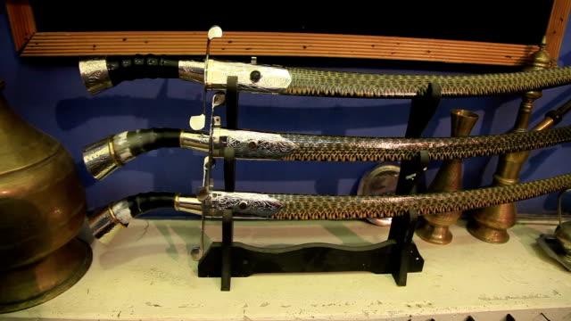 vídeos de stock, filmes e b-roll de sabre with a handle made of animal horn and foot snake skins. - antiquário loja