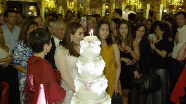 Sabrina Ho blows candles on cake at her birthday party at Oscar Wilde Bar Hotel Cafe Royal on September 12 2016 in London England