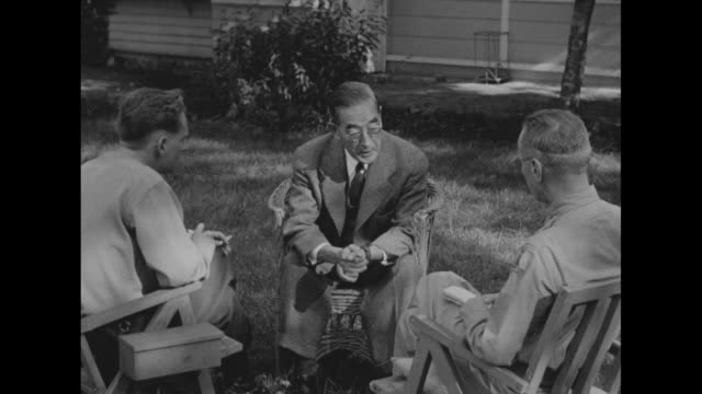 MS Saburo Kurusu sitting in a wicker chair elbows on knees being interviewed by US Army Lt Breakstone and war correspondent Sidney Whipple in a...