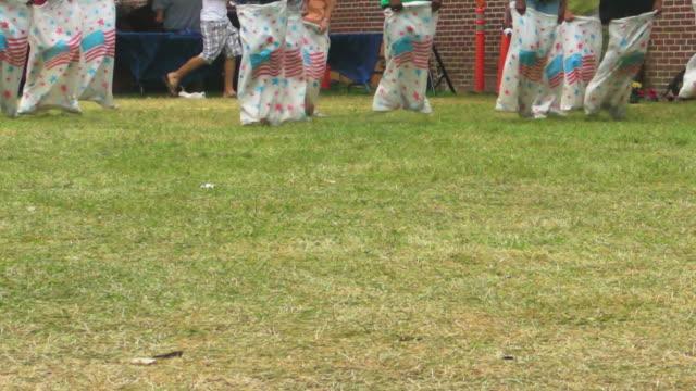 corsa col sacco, festival, divertimento, estate all'aperto, sport, bambini - sacca video stock e b–roll