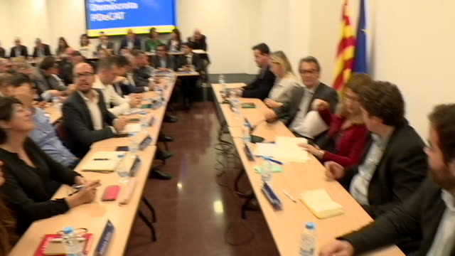 Sacked Catalonia government officials meeting in a crowded party conference room after the Spanish government banned them from the government building