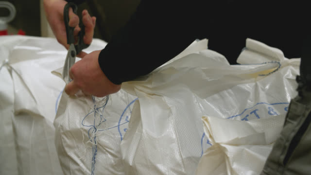 sacks of malt are cut open with scissors in a brewery - shears stock videos & royalty-free footage