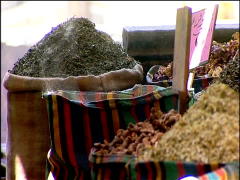 Sacks of spices at market breeze blows and powder is swept into air Egypt
