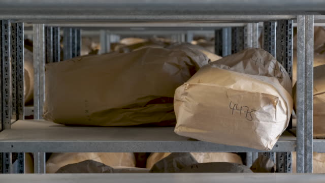 vídeos de stock, filmes e b-roll de sacks of torn documents of the former east german secret police the stasi lie in storage at a facility of the federal commissioner for the records of... - privacidade