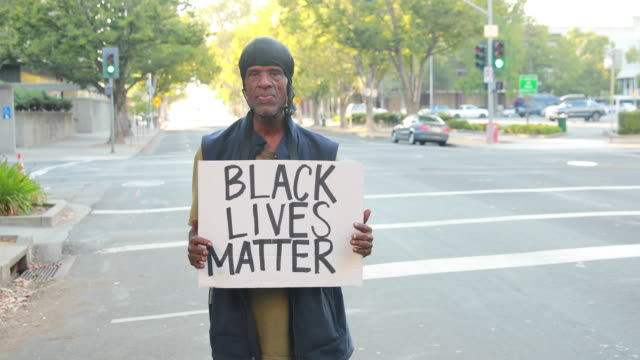 stockvideo's en b-roll-footage met an african american man holds a sign reading black lives matter black lives matter sacramento protesters and allies protest at the office of the... - black lives matter