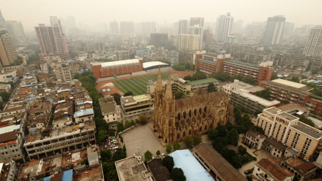 vídeos de stock e filmes b-roll de sacred heart cathedral in guanghzhou from above. wide shot with skyline on a smoggy day - campo de futebol